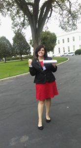 """Allison Plattsmier strikes the pose used in the """"Guns Out"""" social media campaign in front of the White House"""