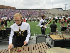 John Collyer, student president of the Spirit of Gold, plays xylophone during a home game this season.