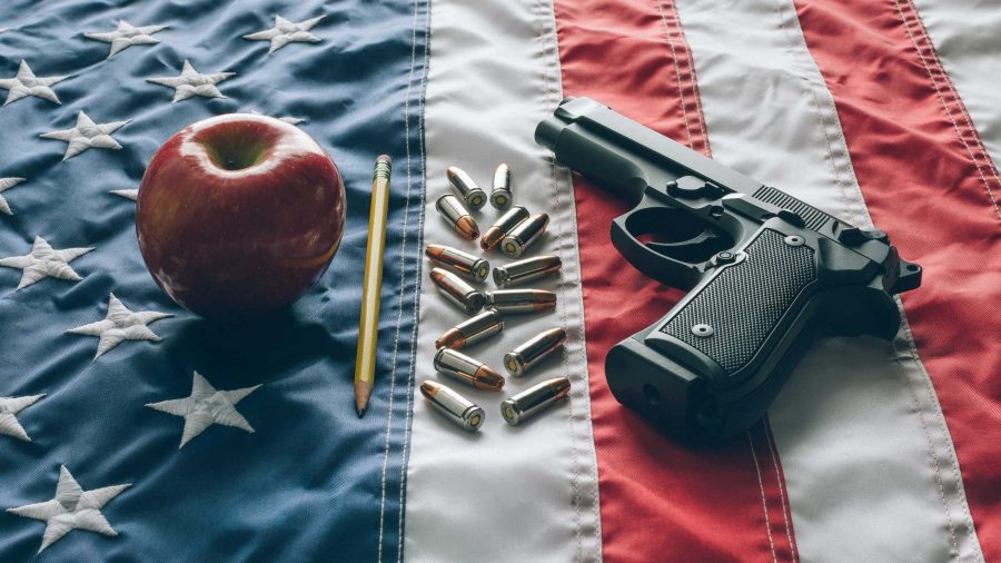 9mm+Beretta+92FS+type+handgun+with+apple+and+pencil+and+ammunition+over+the+USA+Flag+depicting+the+question+whether+to+arm+teachers+in+the+classroom+to+defend+students+against+active+shooters.