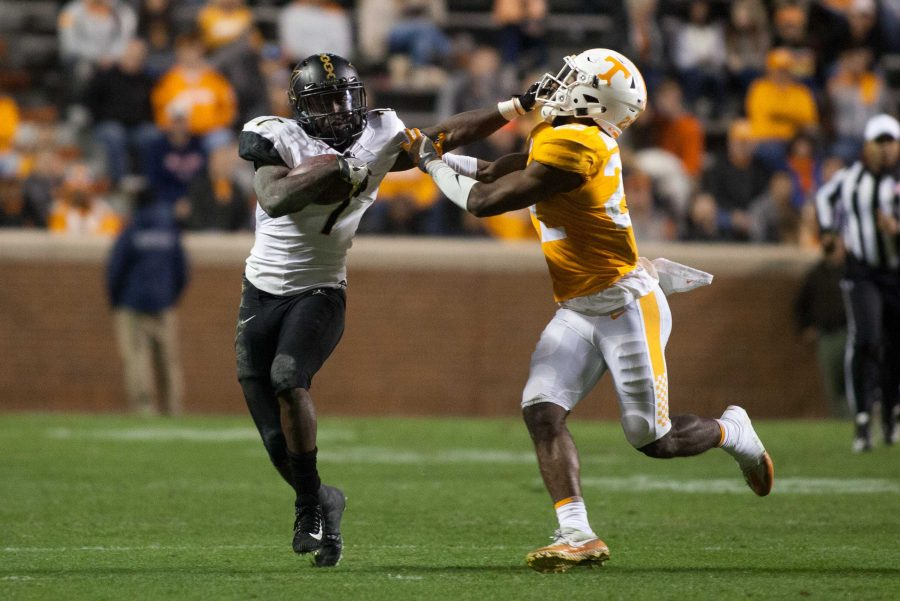 Vanderbilt runningback Ralph Webb delivers a stiff-arm to a Tennessee defender. Photo by Clay Leddin // The Vanderbilt Hustler