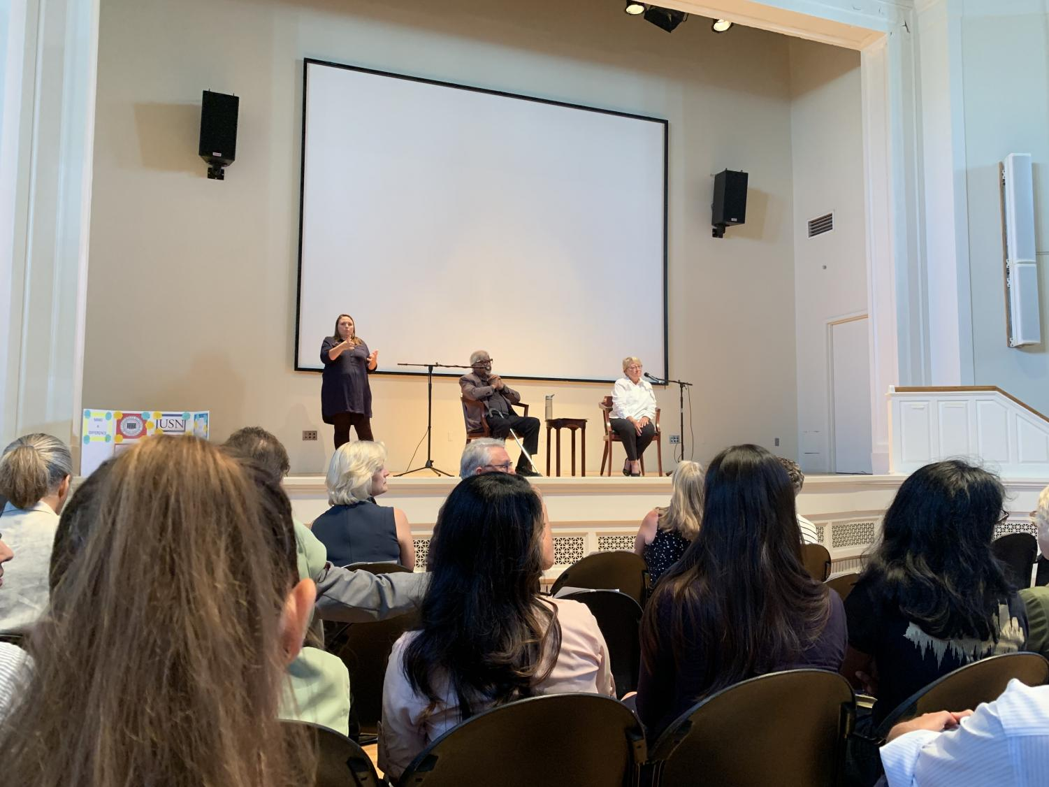 Arun Gandhi on stage with Associate Dean of Human and Organizational Development Sharon Shields and a sign language interpreter in Wyatt Center. (Photo by Immanual John Milton)