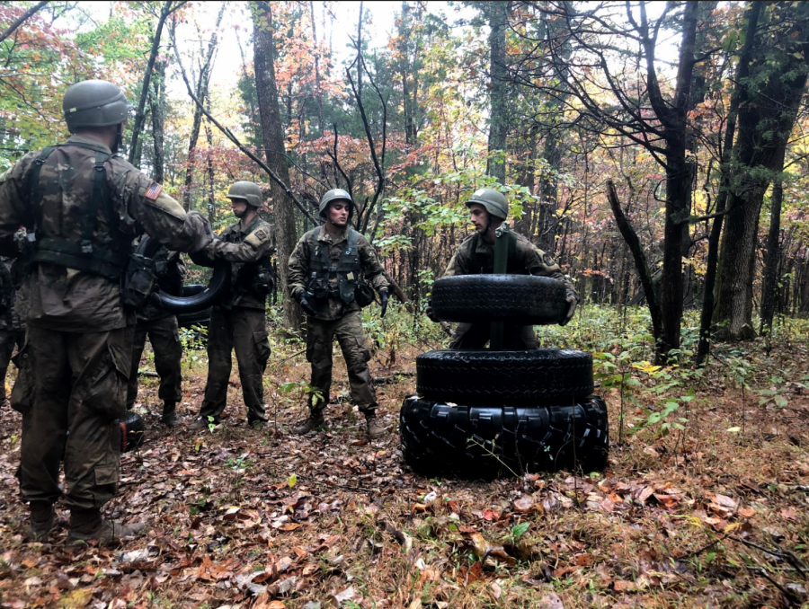 """Cadets competing in the """"Tower of Tires"""" challenge, a timed puzzle with strict rules in which numbered tires of varying sizes and weights must be transferred from pillar to pillar (Photo by Thomas Hum)"""