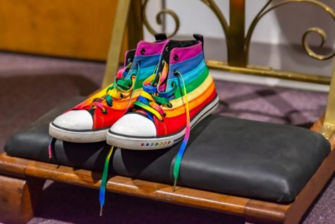 Rainbow striped high-top Converse sitting on church pew bench
