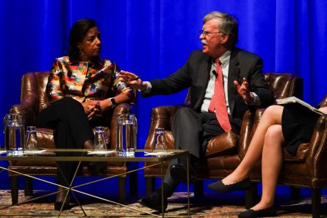 John Bolton leans in over susan rice over a table to talk