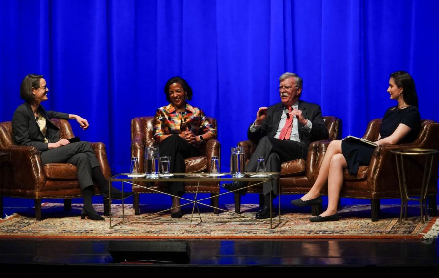 Susan Rice and John Bolton sit with the moderators to discuss issues in leather chairs on top of a rug in Langford Auditorium