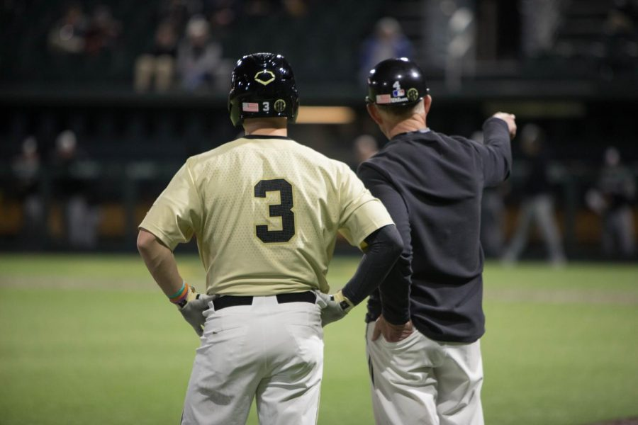 Cooper Davis (left) and Tim Corbin (right) share a conversation at third base.