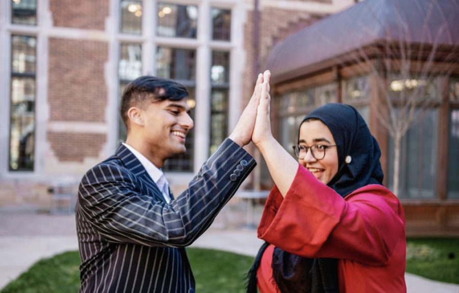 Veer Shah and Shun Ahmed high five on campus