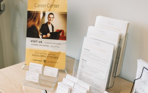 Career center pamphlets on display on a table, one of which features a smiling student