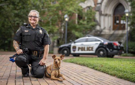 Officer kneeling next to Levi on Vanderbilt's campus