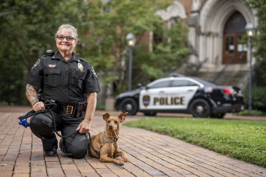 Officer kneeling next to Levi on Vanderbilt's campus