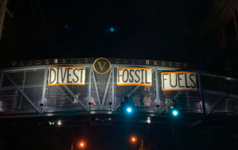 Student activists hang signs on the Commons Bridge demanding divestment. (Photo courtesy of Dores Divest)
