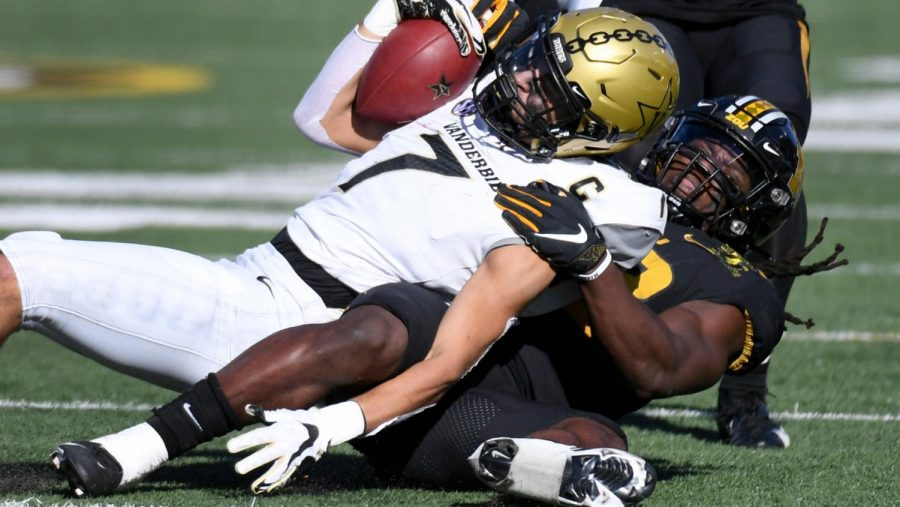 Cam Johnson (7) is pulled down by Missouri linebacker Nick Bolton on Nov. 28, 2020. (AP Photo/L.G. Patterson)