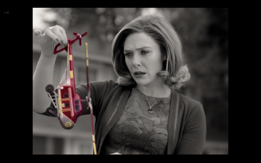 """Unexplainable things begin to happen in Westview in the first two episodes of Marvel Studios' """"WandaVision,"""" like when Wanda stumbles upon a toy helicopter tangled in her rose bushes—a colorful contrast to the black-and-white world of 50s and 60s television. (Marvel Studios/WandaVision)"""