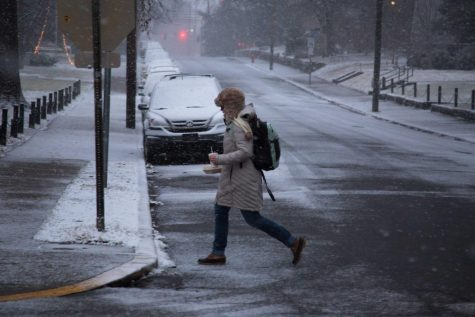 Student crosses the street in snow