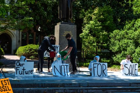 "people sit in front of the Vanderbilt statue holding signs that say ""Our Future Not For Sale"" wearing white body suits and having mock oil poured on them by people in black clothing"