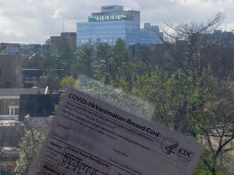 a covid-19 vaccine card is held against a window overlooking light hall