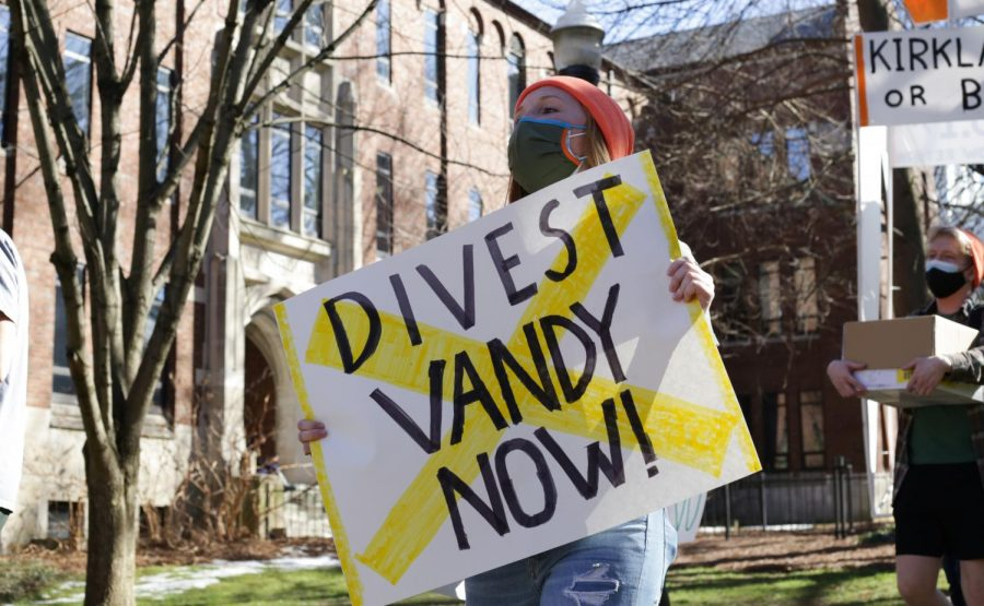 woman+holding+white+sign+that+reads+%22divest+vandy+now%22+with+a+yellow+X+over+the+front