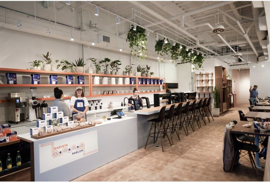 Barista Parlors coffee-centered set-up features a long row of bar chairs and two-seater tables against the opposing wall.