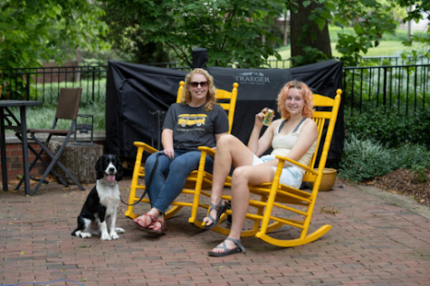 elizabeth pendergrass sitting with her dog and daughter in rocking chairs outside West House