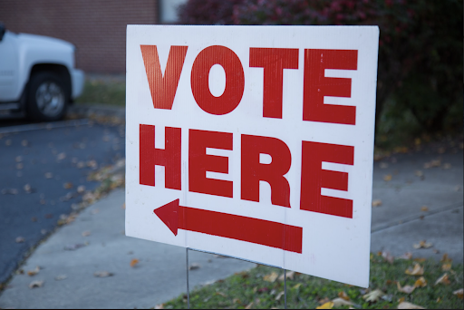 sign that says vote here in red with an arrow
