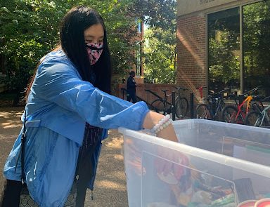 student putting stuff in a bucket outside Rand for the donation drive
